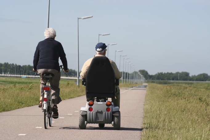 older-couple-on-bike-and-wheelchair-istock