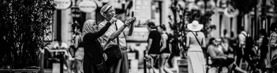 An older couple looking at a smartphone in a historic city